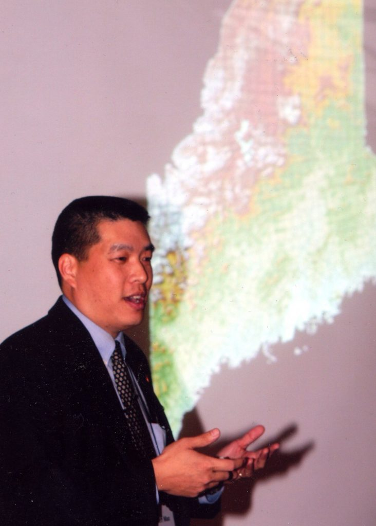 Jeff Mao presenting in front of a map of the state of Maine
